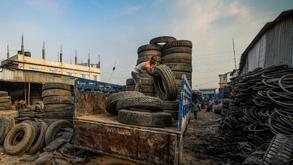 A labourer unloads used tyres from a truck in Dhaka on Sept 19, 2019.